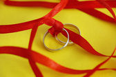 Wedding rings with red ribbon — Stock Photo