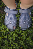 Child's legs on green grass — Stock Photo