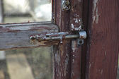 Old latch on the abandoned glass door — Stock Photo