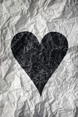 Crumpled paper with black heart — Stock Photo