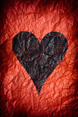 Crumpled red paper with black heart — Stock Photo