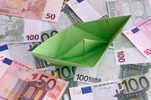 Green paper boat on Euro banknotes — Stock Photo