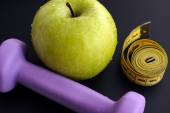 Dumbbell and green apple with tape measure — Stock Photo