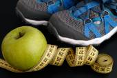 Sport shoes and apple with tape measure — Stock Photo