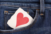 Paper pink heart in a pocket of blue jeans — Stock Photo