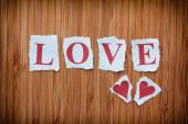 Word Love and two paper hearts on wooden texture background — Stock Photo