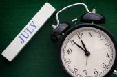 Black alarm clock and word July — Stock Photo