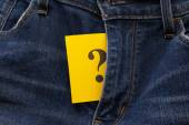 Yellow paper note with question mark appears out in jeans fly — Stockfoto