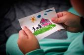 Child holds a drawn house with family — Stock Photo