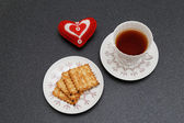 Cup of tea, cookies and red heart — Stock Photo