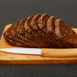 Grain brown bread, sliced on the wooden plate — Stock Photo #67831229