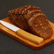 Grain brown bread, sliced on the wooden plate — Stock Photo #67831237