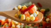 Closeup spoon with frozen mixed vegetables — Stock Photo