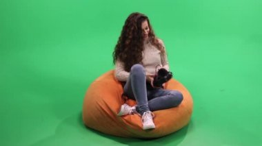 Girl sitting at bean bag and listening music in headphones, relax and smiling, green Screen. — Stock Video