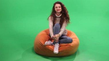 Girl sitting on bean bag, relax ans smile — Stock Video