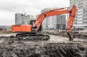 Orange excavator on a construction site — Stock Photo