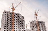Two moving yellow cranes over unfinished house — Stock Photo