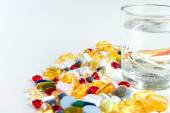 Colorful pills and glass of water, on white background — Stock Photo