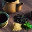 Ceramic teapot, cup of black tea with mint leaves and brown sugar on wooden table — Stock Photo #61693893