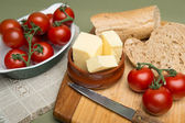 Bread and butter, Delicious organic home made bread and butter with ripe tomatoes on wooden board — Stockfoto