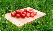 Fresh cherry tomatoes on the old wooden cutting board, closeup food, outdoors shot — Stock Photo