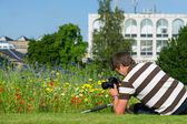 Young handsome caucasian photographer, videographer in botanic gardens — Stock Photo