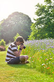 Young handsome caucasian photographer in botanic gardens — Stock Photo