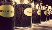 Glass jars with different flavour coffee on display — Stock Photo