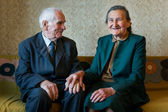 Cute 80 plus year old married couple posing for a portrait in their house. Love forever concept. — Stock Photo