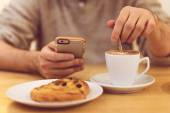 Always in touch. Detail image of unrecognizable man drinking coffee and holding smart phone while having breakfast in restaurant. — Stock Photo