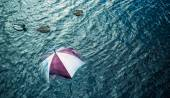 Raining too much? Escape the bad weather, vacation concept. Umbrella swimming in water. — Stock Photo