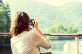 Unrecognizable young female enjoying boat ride, taking photographs, Loch Katrine, Scottish Highlands, UK — Stock Photo