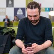 Handsome young man with dreadlocks using his phone at an airport lounge. — Stock Photo #62803725