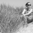Young woman sitting in sand dunes amongst tall grass relaxing, enjoying the view on sunny day, Luskentyre, Isle of Harris, Scotland — Stock Photo #62861551