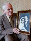 Handsome 80 plus year old senior man holding his wedding photograph. Love forever concept. — Stock Photo