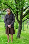 Beautiful 80 plus year old senior woman posing for a portrait in her garden. — Stock Photo