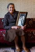 Beautiful 80 plus year old senior woman holding her wedding photograph. Love forever concept. — Stock Photo