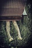 Dirty female legs stickig out from under an armchair in a field, dark mood unusual concept — Stock Photo
