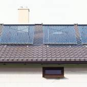 Vacuum solar water heating system on a house roof. — Stock Photo