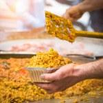 Man serving traditional spanish chicken paella, food market — Stock Photo #71944297