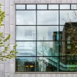 Modern office building exterior with many windows, reflexions and trees — Stock Photo #73035333