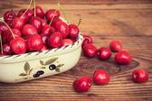 Ripe organic homegrown cherries in a vintage ceramic bowl, on wooden background — Stock Photo