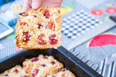 Hand taking a piece of sweet homemade cherry pie with crumble — Stock Photo
