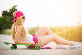 Adolescente atraente hipster com skate, imagem com sunflare — Fotografia Stock