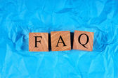 Cubes with an inscription FAQ on crumpled blue paper. Top view. — Stock Photo
