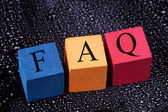 Colorful cubes with an inscription FAQ on black dirty chalkboard. — Stock Photo