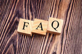 Cubes with an inscription FAQ on the old boards. Top view. — Stock Photo
