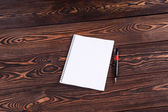 Notebook with pen on brown table — Stock Photo