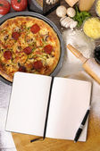 Pizza with notebook and ingredients — Stock Photo
