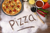 The word Pizza written in flour with various ingredients. — Stock Photo